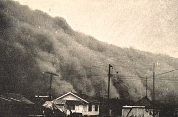picture of a dust storm from the dust bowl overwhelming a town